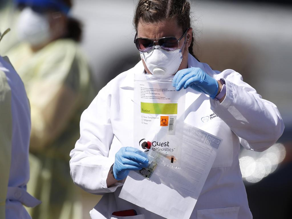 A medical technician carries a plastic envelope containing a vial with a swab used for a test. Picture: AP