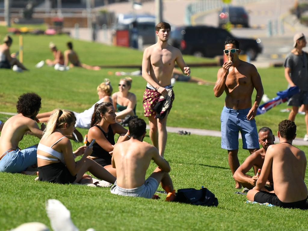 Bondi Beach is closed, but tourists continued to gather on the grass nearby on Tuesday. Picture: AAP
