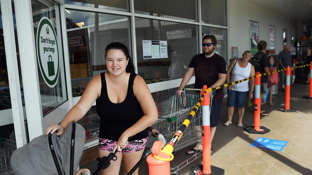 PATIENT SHOPPERS: Ashleigh Peters waited in line at Woolworths Pialba in compliance with social distancing regulations, waiting for her turn to be called through. Photo: Cody Fox