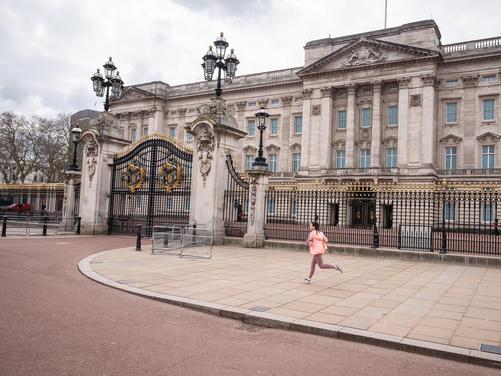A jogger runs along the deserted footpaths around Buckingham Palace. Picture: Getty Images