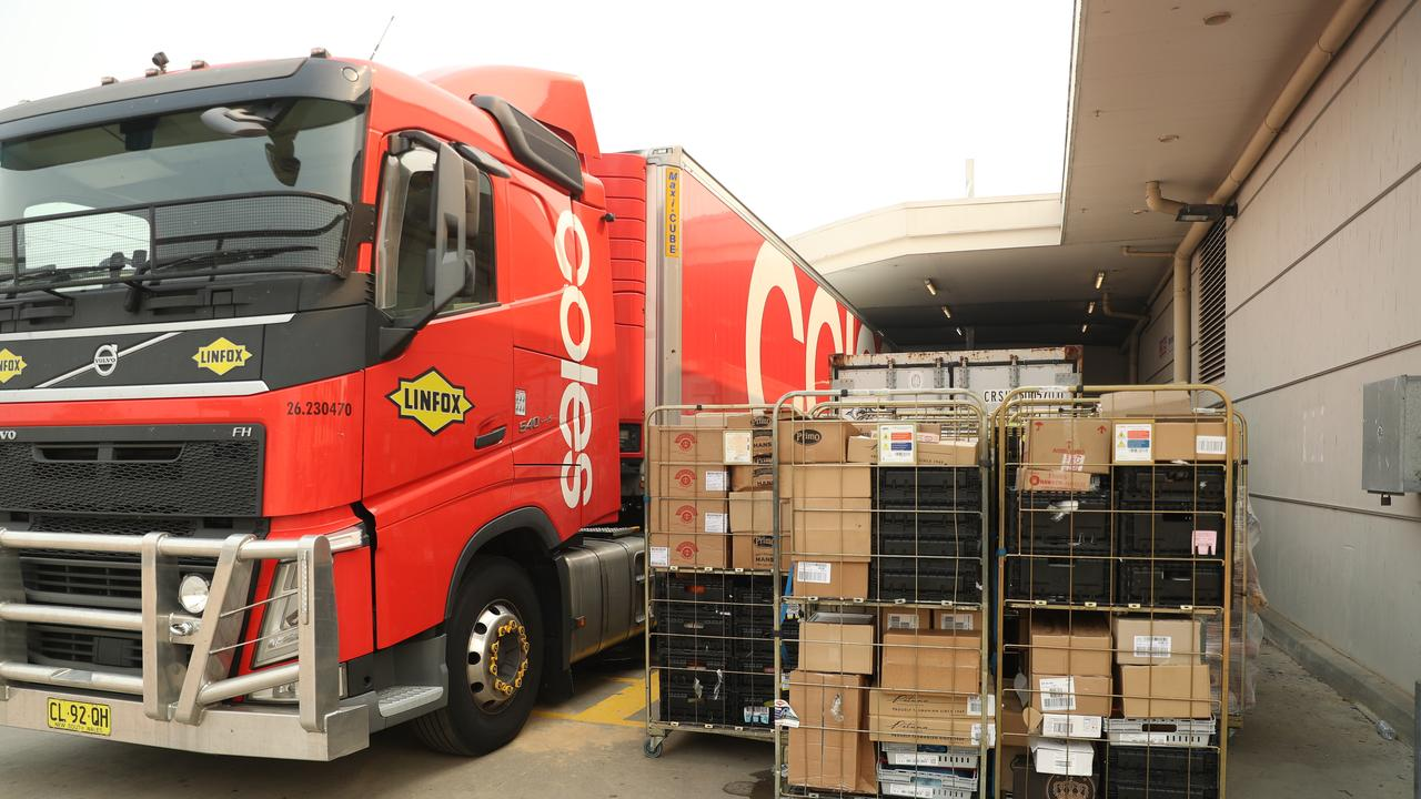 Coles trucks line up at the loading dock in Batemans Bay to deliver supplies as dump truck disposes of perishable food. picture John Grainger