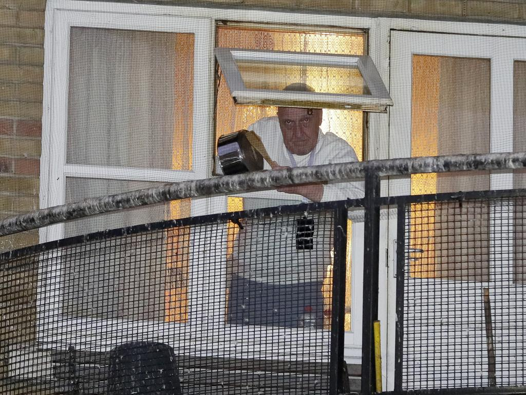 A man knocks a pot from his window near West Middlesex University Hospital to show his support for NHS staff. Picture: AP