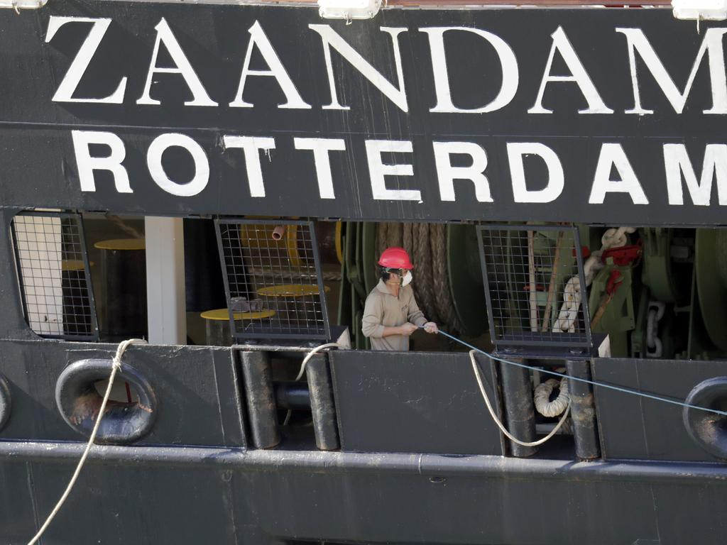 A crew member wearing a protective mask puts out lines as Carnaval's Holland America cruise ship Zaandam arrives at Port Everglades.