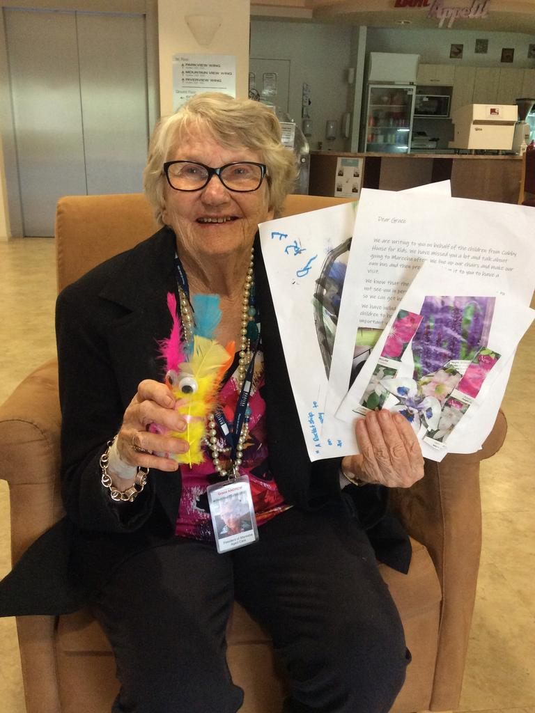 Mareeba Aged Care resident Grace Andrew shows off some of the artwork she received in a package sent from Cubby House for Kids long daycare centre.