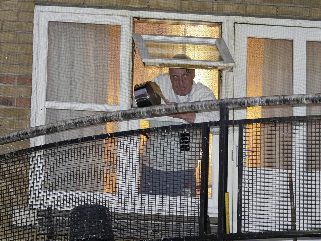 A man knocks a pot from his window near West Middlesex University Hospital to show his support for NHS staff as the country is in lockdown to help curb the spread of the coronavirus, in London.