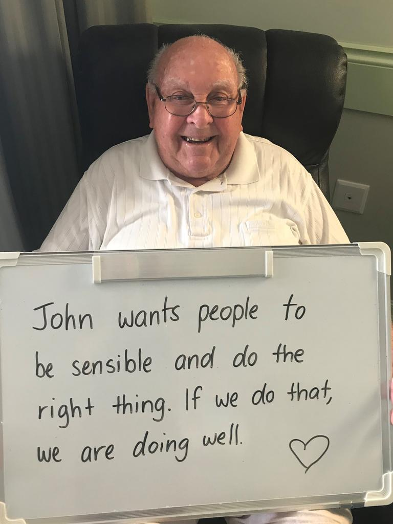 Mareeba Aged Care resident John Cookson shows off his message that was shown through their Facebook page.