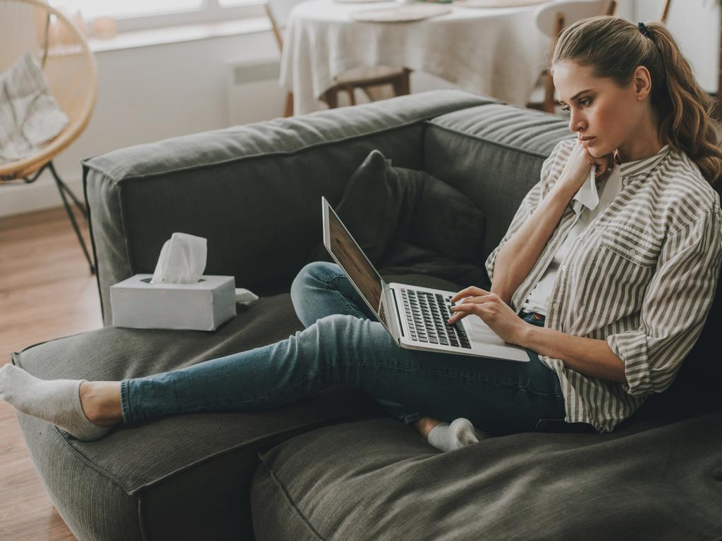 Early symptoms of disease. Side on full length portrait of tired sick lady watching medical program on laptop while sitting on sofa with nasal paper wipes Picture: Istock