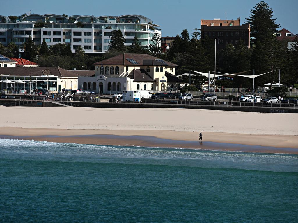A lone person ignores closed-beach signs to go for a walk along Bondi Beach on Sunday.