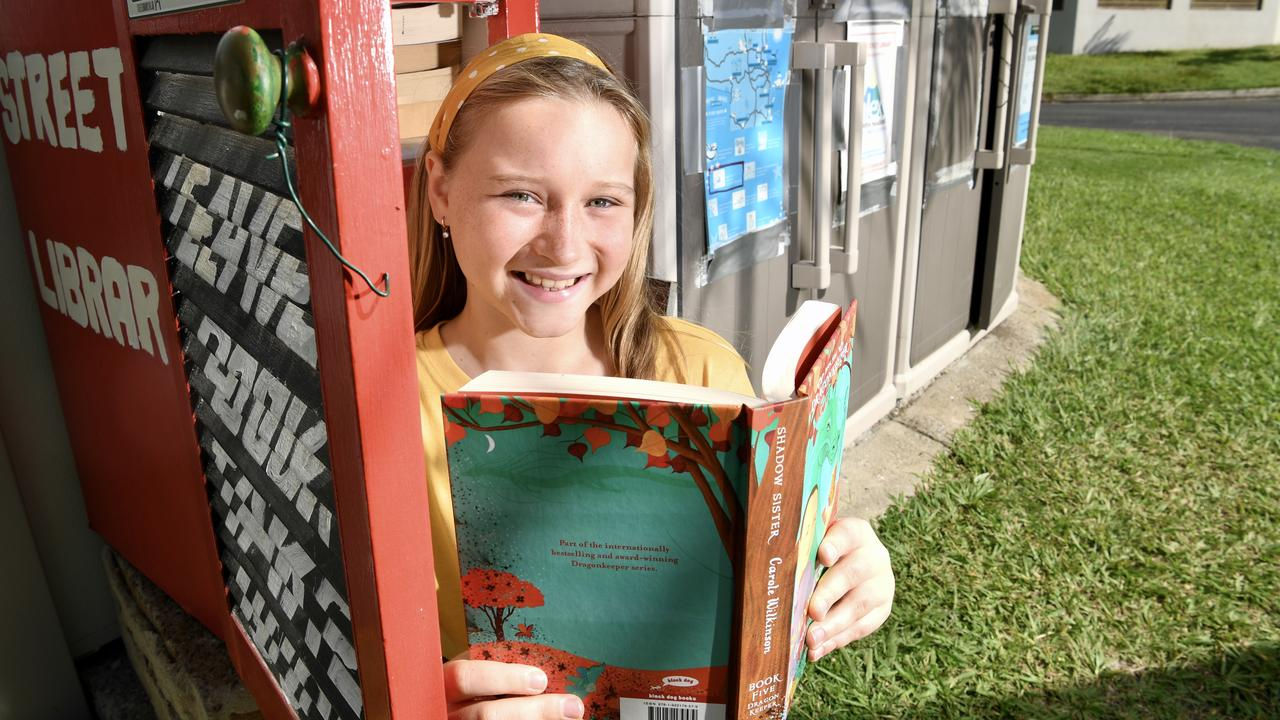 STREET LIBRARY: The Alex Street Library is open for business and Phoebe Clewett, 11, couldn't be happier. Photo: Warren Lynam