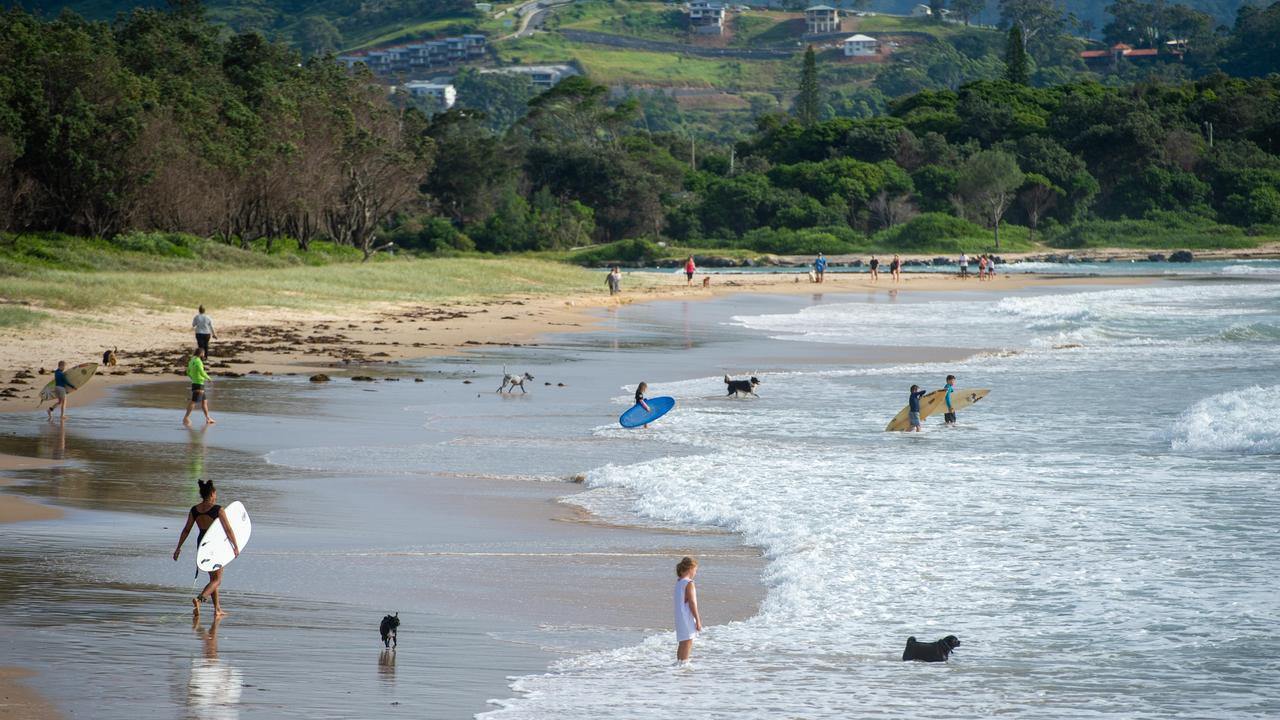 Walkers and surfers on North Wall beach in Coffs Harbour this week. Photo by Trevor Veale