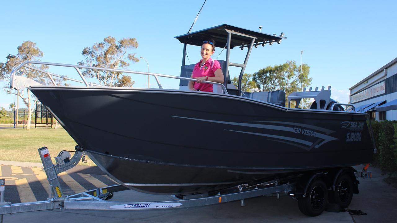 Event co-ordinator Rebecca Long shows off the Boyne Tannum HookUp major prize, a Sea Jay 630 Vision