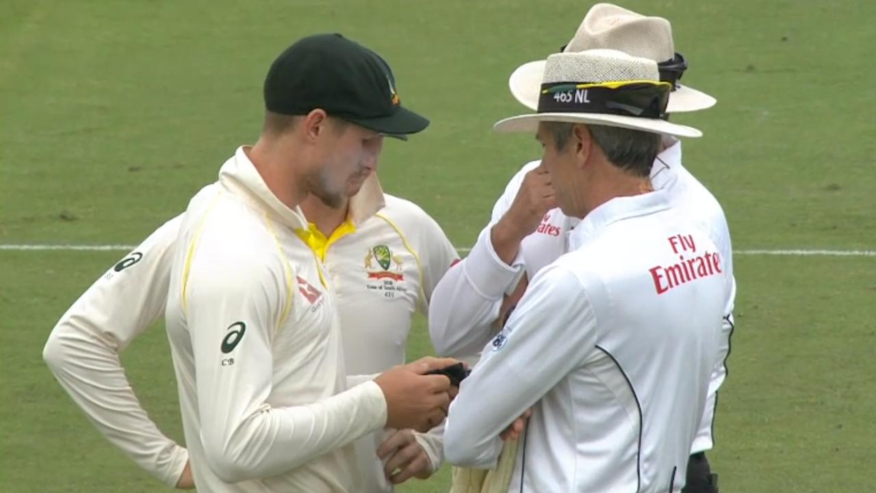 Cameron Bancroft shows the umpires his sunglass cloth after he was accused of cheating in South Africa.