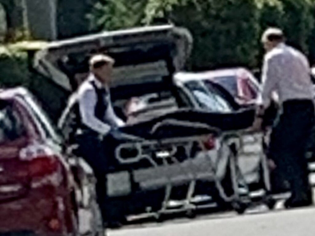 The hearse comes to take away the bodies of a mother and her young son after a horrific unit complex fire at Biggera Waters this morning.