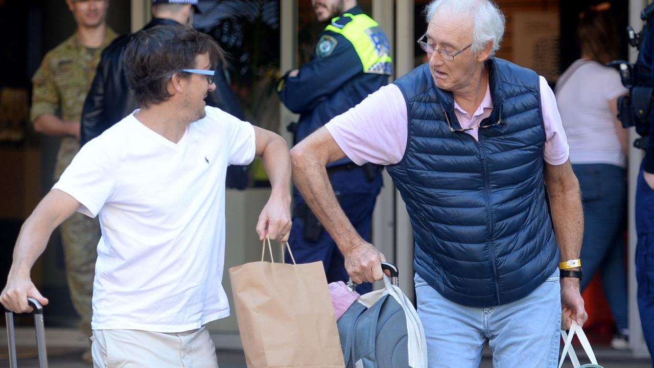 Keen to be reunited (but not so keen to compromise social distancing), Peter O'Connel (right) is greeted by a friend after being released from quarantine in Darling Harbour. Picture: Jeremy Piper.