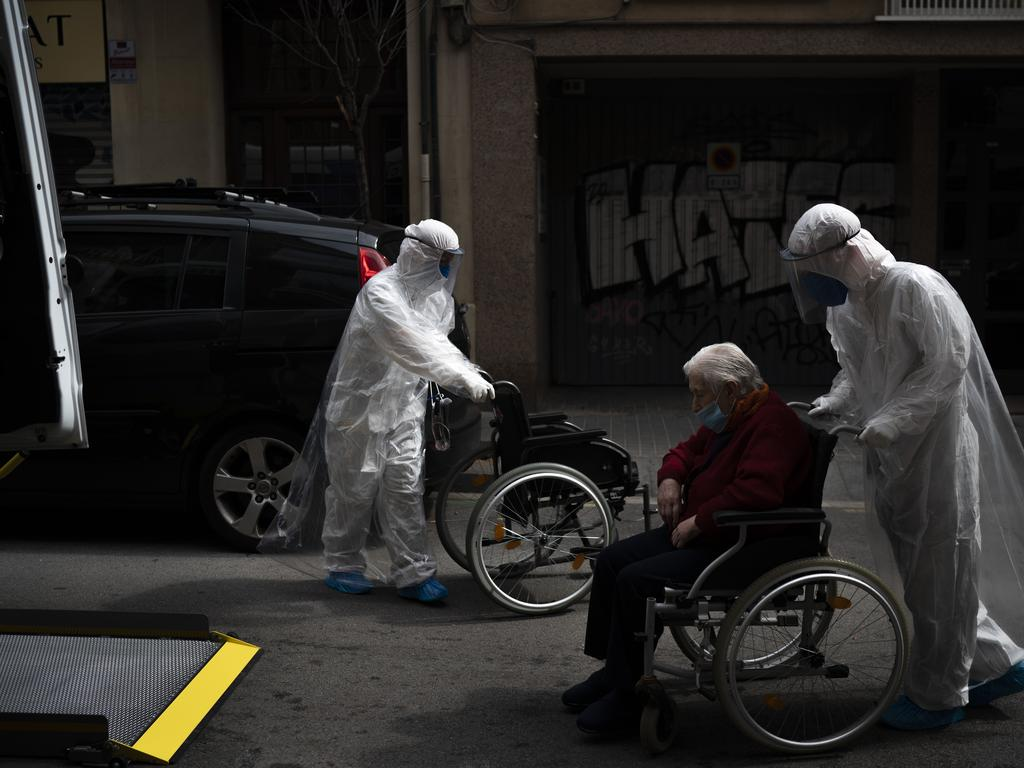 A volunteer of the Spanish NGO Open Arms pushes in a wheelchair an elderly resident of a nursing home with coronavirus symptoms to a Barcelona hospital. Picture: AP