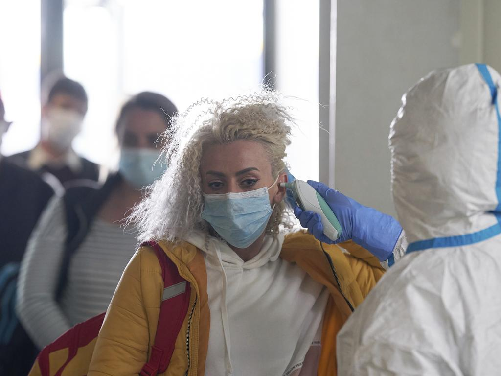 A woman gets her temperature checked in Germany.