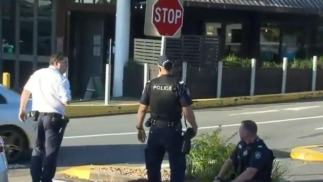 A police officer waits to be checked by paramedics after the arrest at Benowa Gardens Shopping Centre on Tuesday afternoon. Picture: Nine News Gold Coast