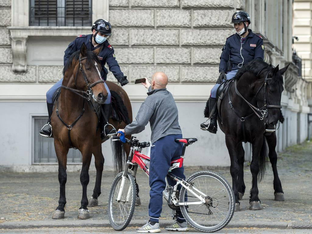 Italian police talk to a cyclist in Rome. The country remains in complete lockdown. Picture: AP