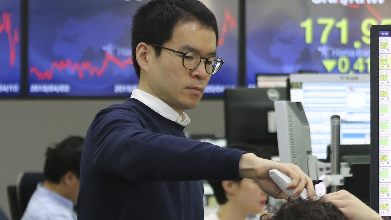 A currency trader checks the temperature of his colleague at the foreign exchange in Seoul. Picture: AP