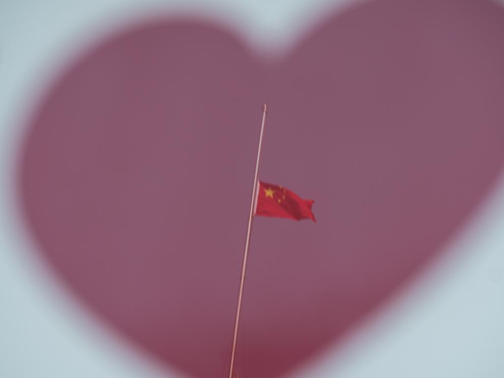 A reflector shows The Chinese national flag flies at half-mast at the Bund to mourn victims of COVID-19 on April 04, 2020 in Shanghai, China. Picture: Getty