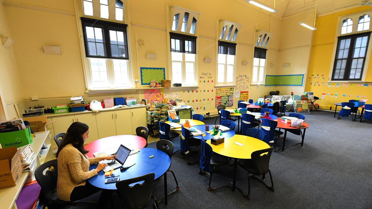 A teacher is seen in an empty class room at a primary school in Melbourne's inner north. Victorian Premier Daniel Andrews has said schools can reopen but has encouraged distance learning. Picture: James Ross/AAP