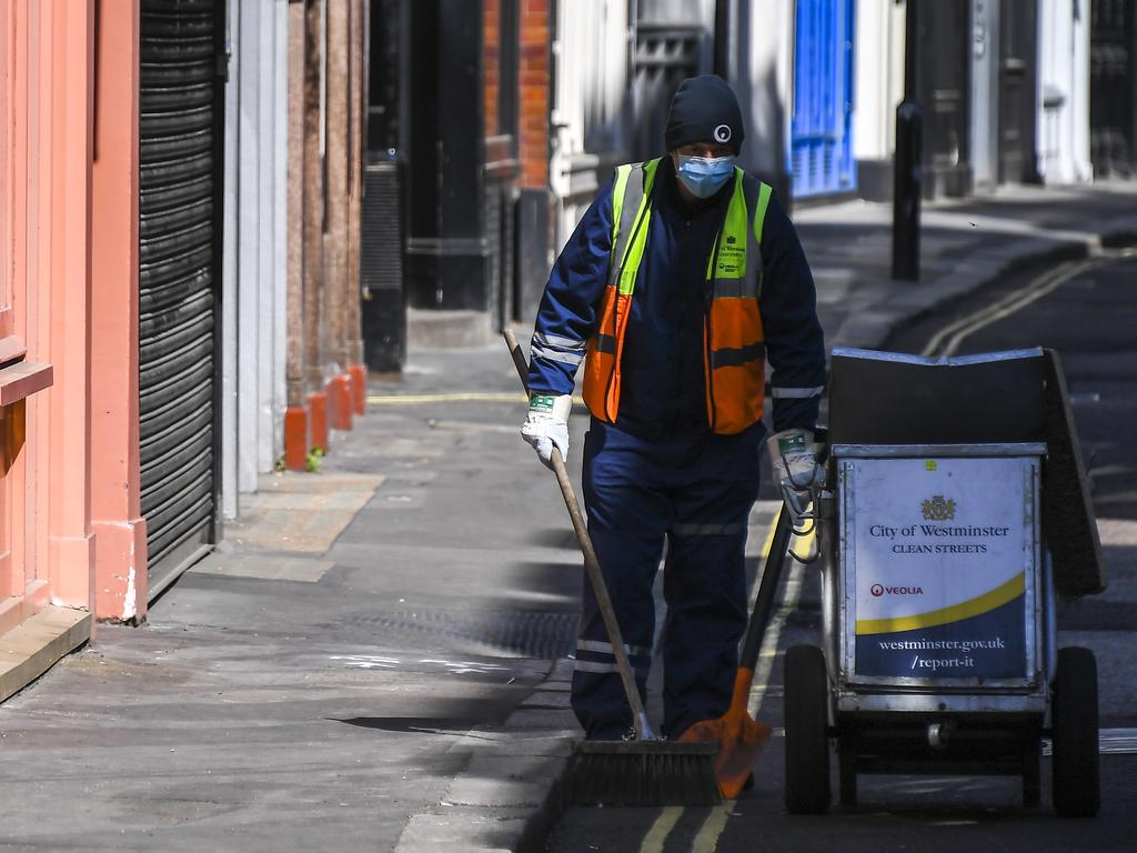 A road cleaner wears a mask in a deserted Carnaby Street in London. Picture: AP