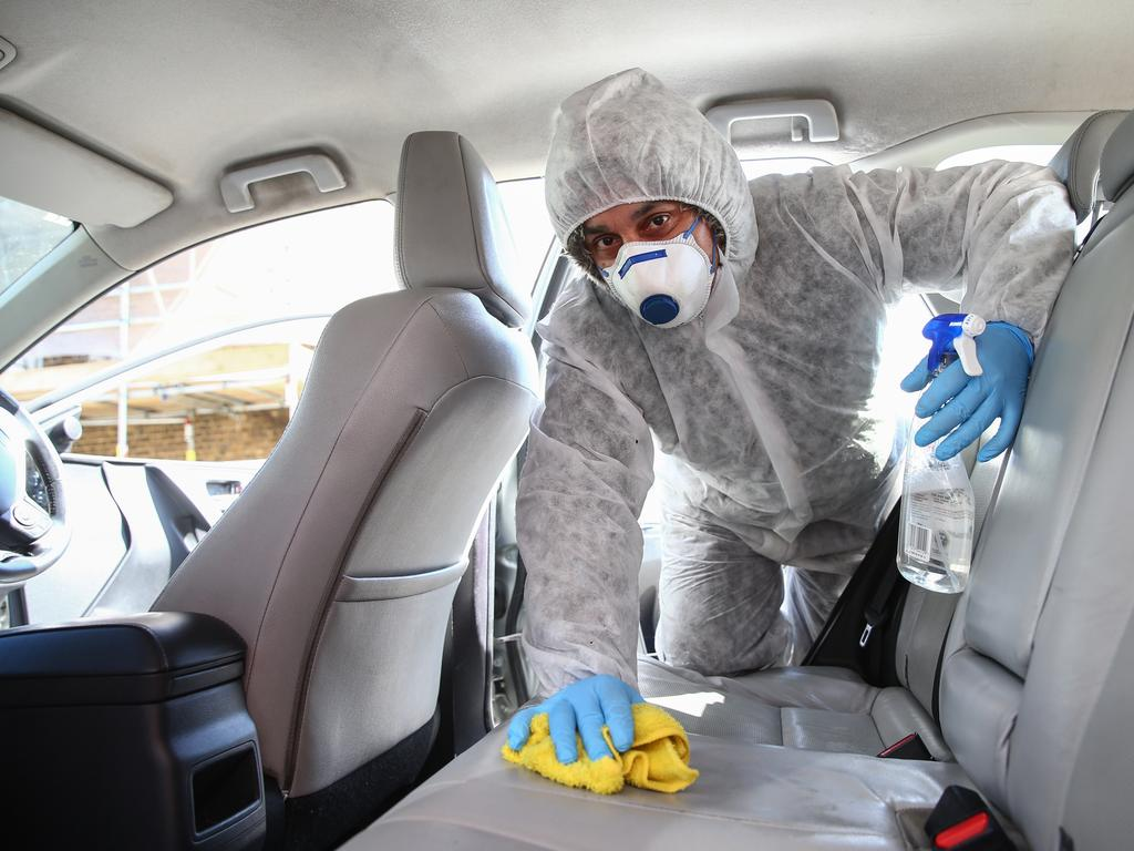 Uber driver Yasar Gorur cleans his car in East London. Coronavirus deaths in the UK could be higher than reported. Picture: Getty Images