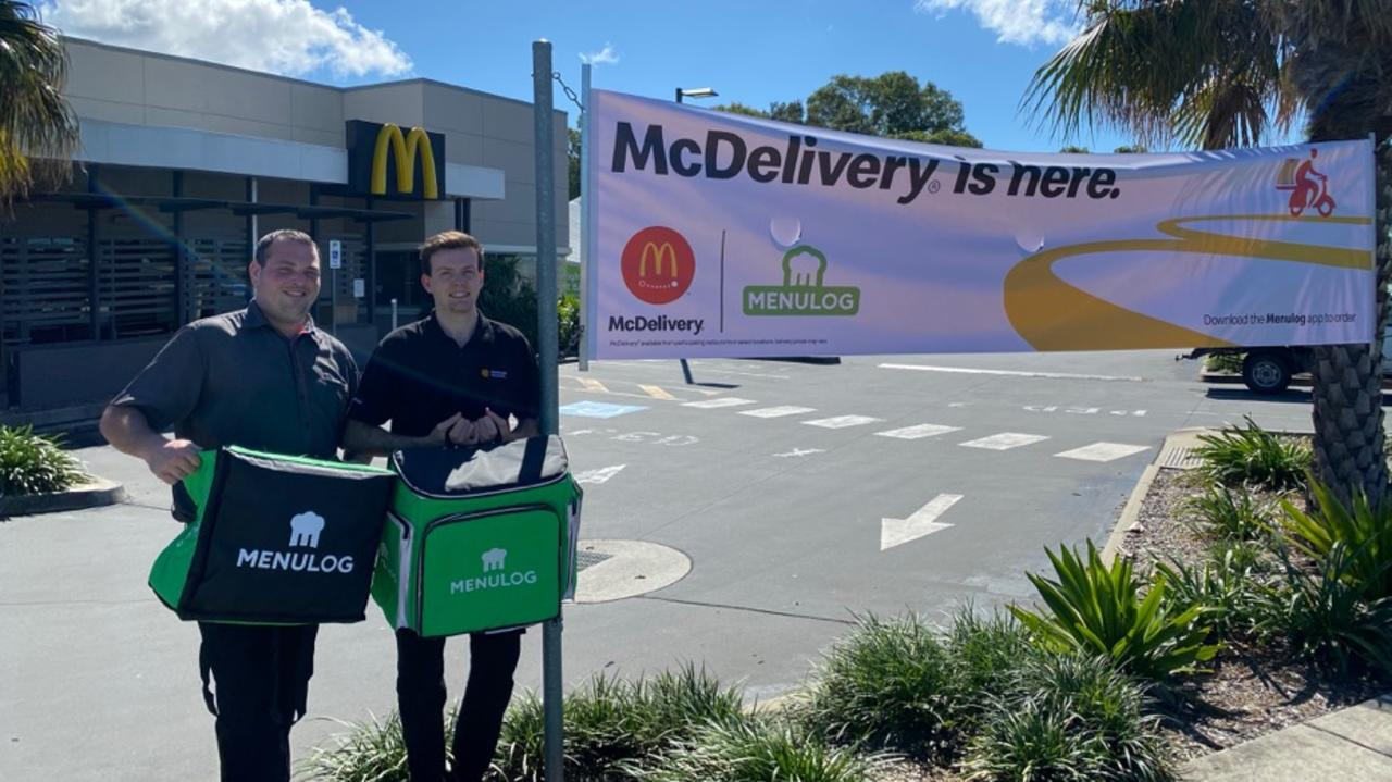 Bribie Island McDonald's management team members Brandon Gaiero and Angus Allison-Powell with the new menulog delivery bags.