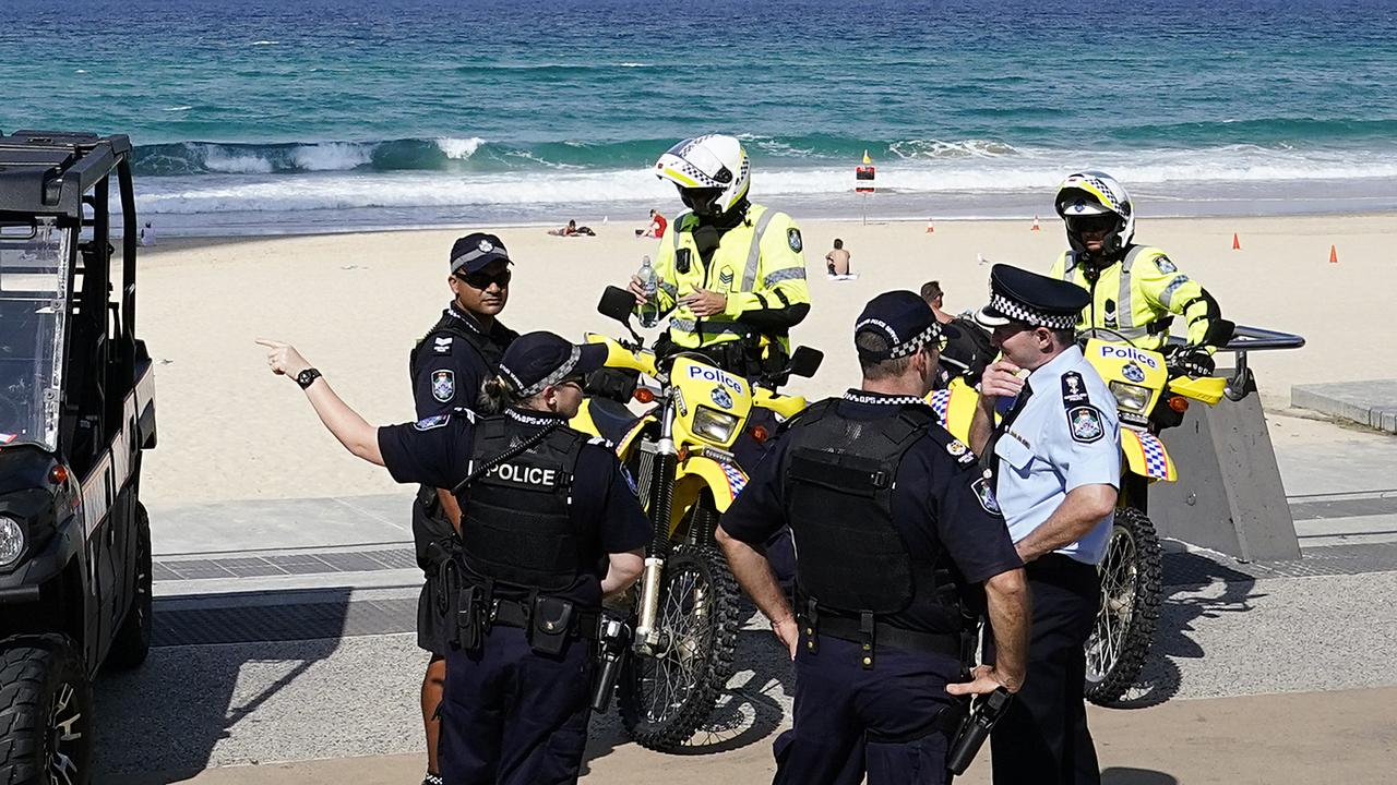 Police are seen gathered at Surfers Paradise Beach. (AAP Image/Dave Hunt)