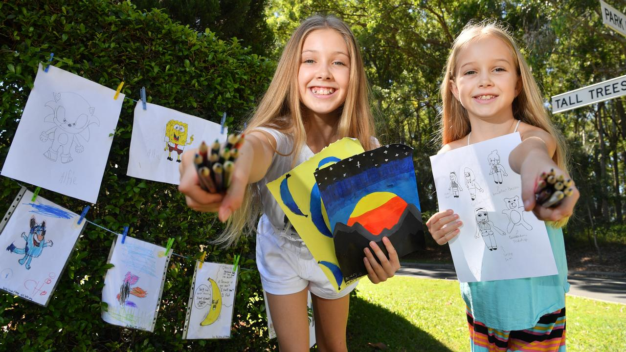 Avery and Deedee O'Mara of Caloundra add artwork to a hedge that encourages children to hang artwork, as a way to spread cheer through the community in isolation. Photo: John McCutcheon