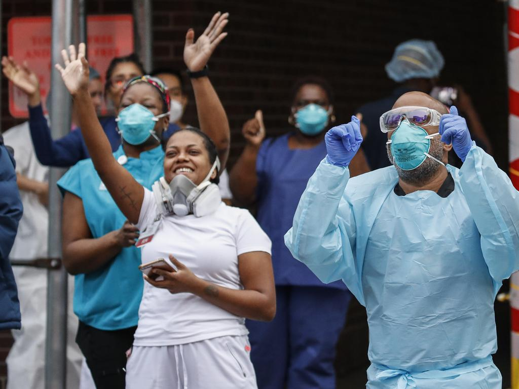 Medical workers cheer and acknowledge pedestrians and FDNY firefighters who gathered to applaud them at 7pm outside Brooklyn Hospital Center, Tuesday, April 14, 2020, in New York. (AP Photo/John Minchillo)