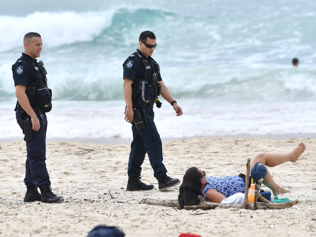Queensland Police are seen moving on a sunbather from the beach at Burleigh Heads on the Gold Coast on Good Friday. Picture: Darren England/AAP