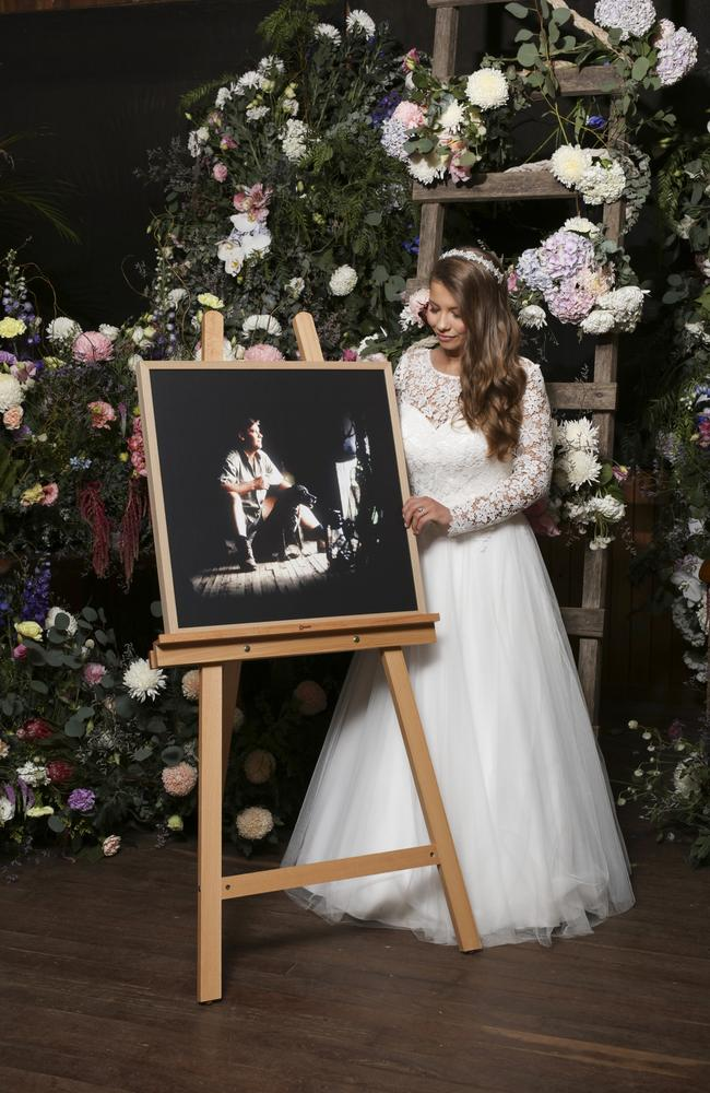 Bindi Irwin standing next to an easel with a photo of her father Steve. Picture: Kate Berry