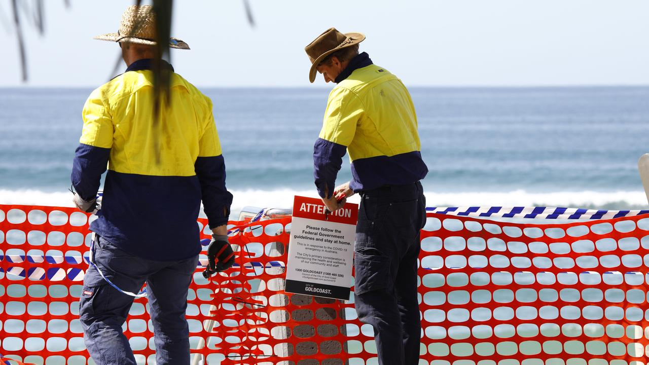 Gold Coast council workers remove the barricades at Surfer Paradise, opening the beaches after the coronavirus caused closure of beaches. Picture: Tertius Pickard