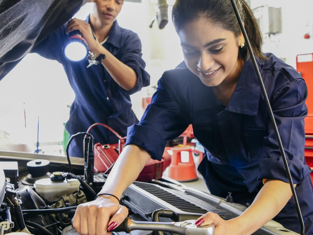 CAREERS FOR AUG 31: Two student mechanics at college repairing car, woman using tool and smiling, man helping by shining light on car engine.