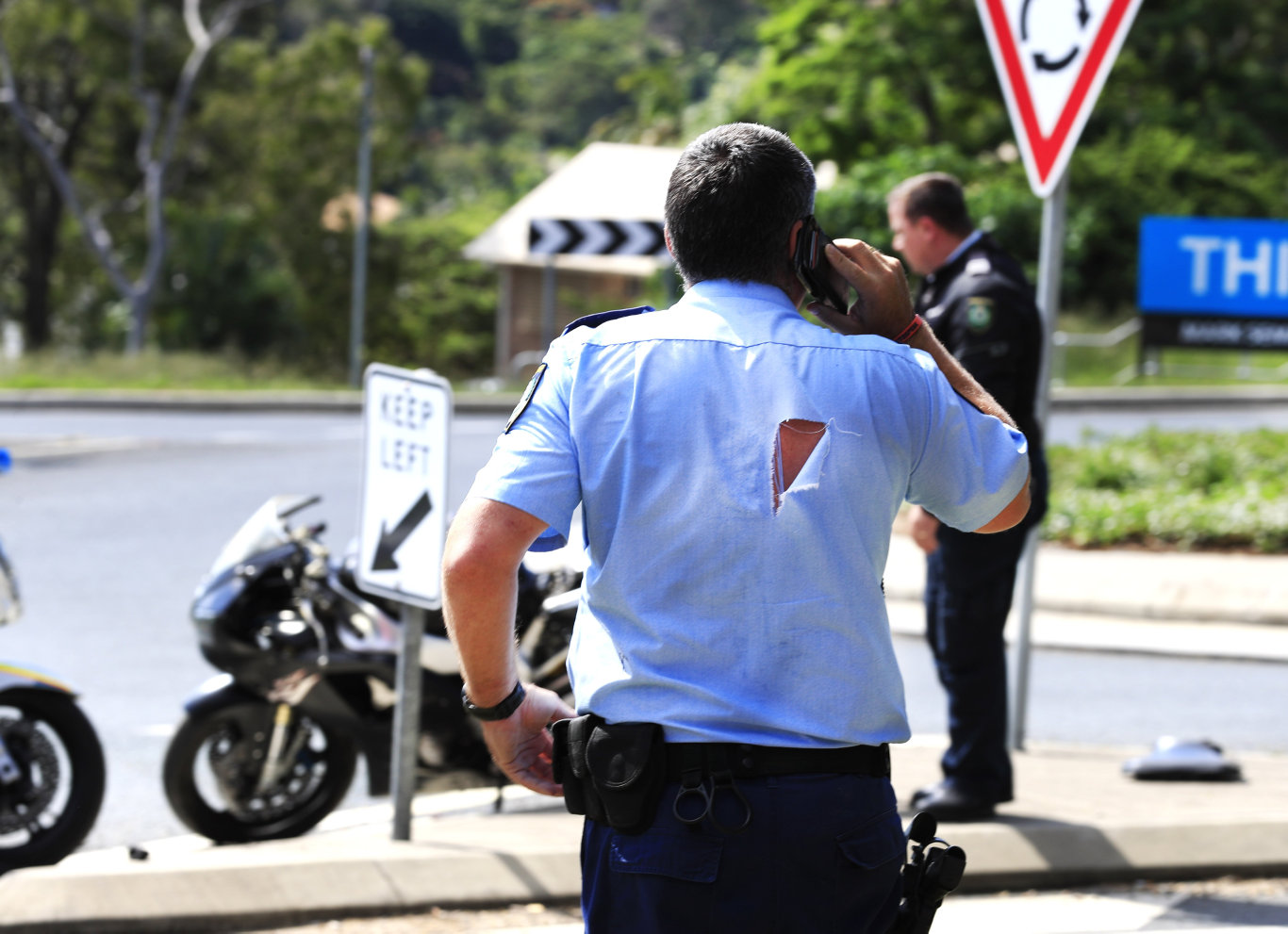 NSW Police inspect an alleged stolen motor bike which Police had been pursuing through Banora Point when it crashed after taking a corner too fast on the corner of Fraser Drive and Terranora Road at Banora Point. Photo: Scott Powick