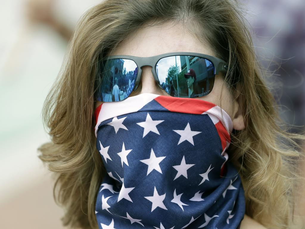 A woman wearing a US flag to cover his face at a rally in Florida, where some want the lockdown to end. Picture: AP Photo/John Raoux
