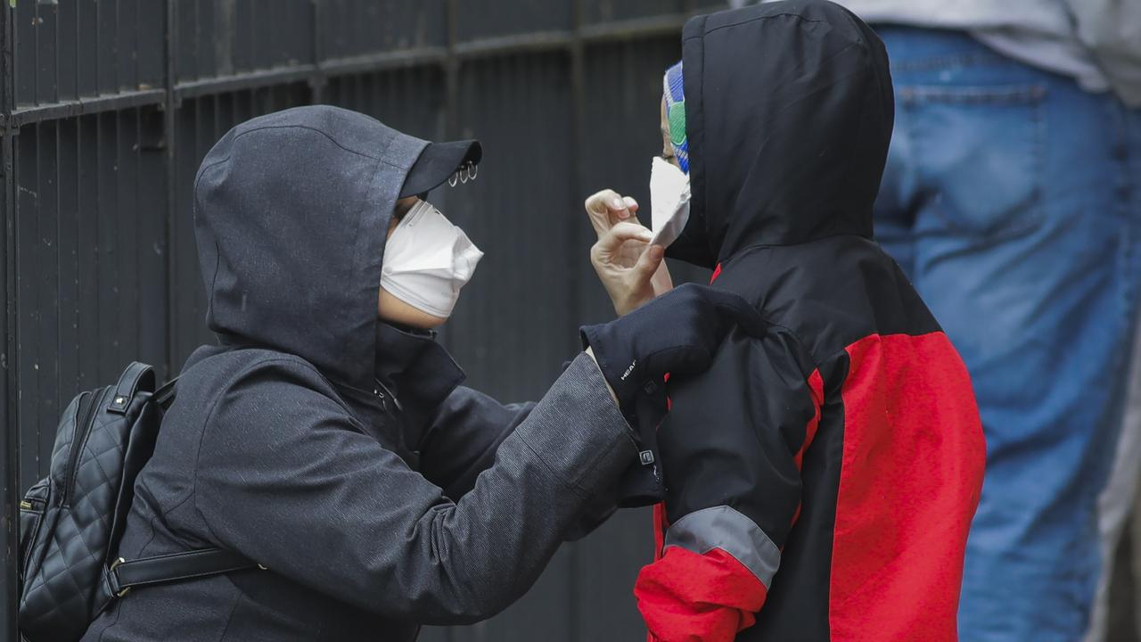 A woman adjusts her child's protective mask as they wait in line to be screened for COVID-19 at Gotham Health East New York.