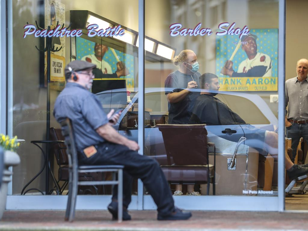 Barber and owner of Chris Edwards wears a mask and cuts the hair of customer as others wait at Peachtree Battle Barber Shop in Atlanta. Picture: AP