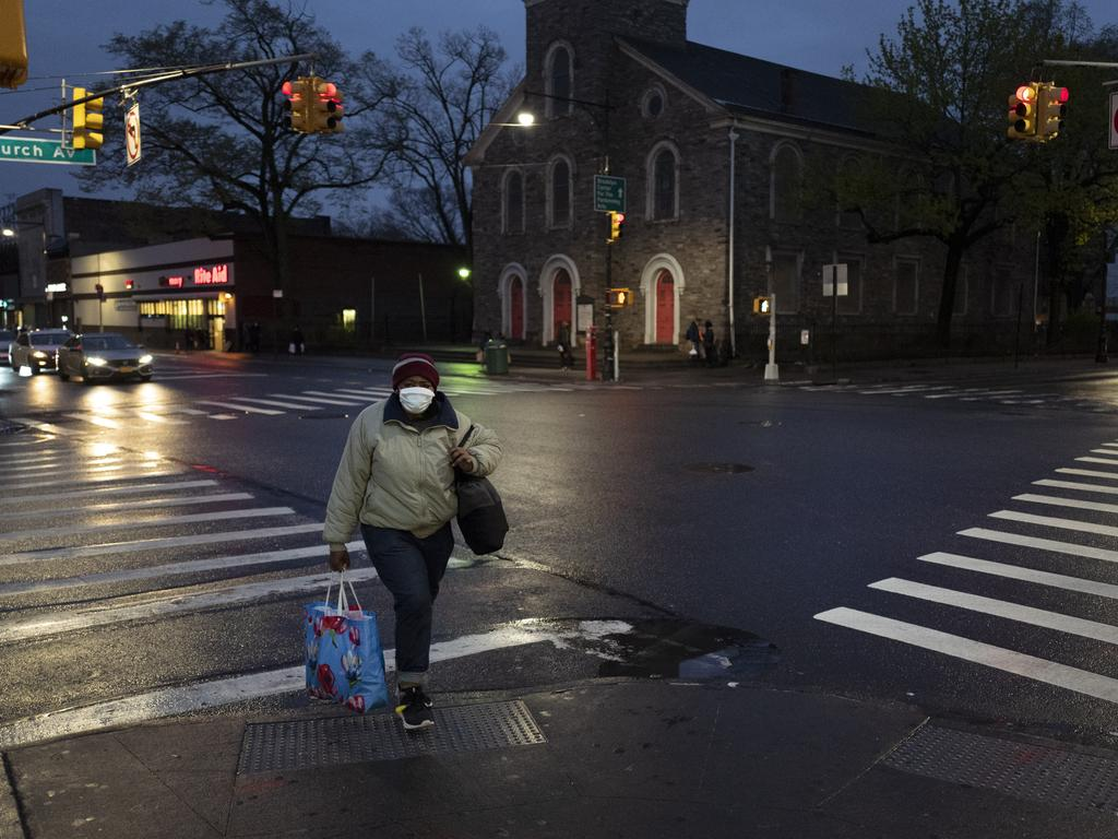 A woman wearing a mask crosses Church Avenue in the Brooklyn borough of New York. Picture: AP