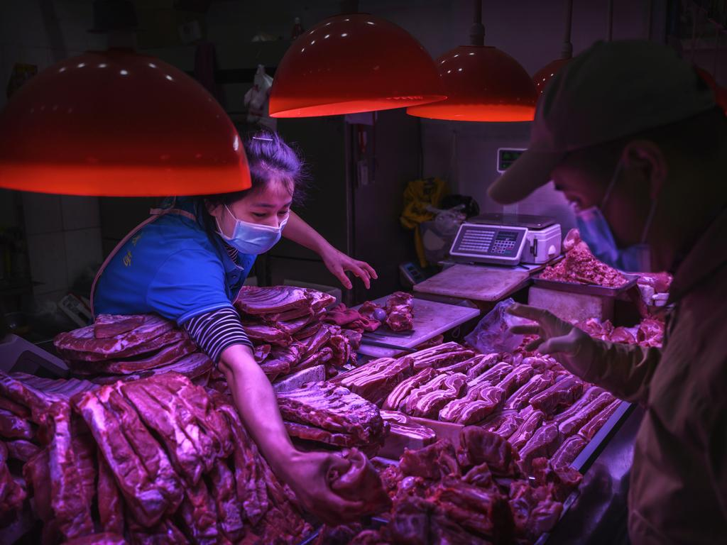 A Chinese meat vendor wears a protective mask as she serves a customer at her stall at a food market in Beijing, China. Picture: Getty