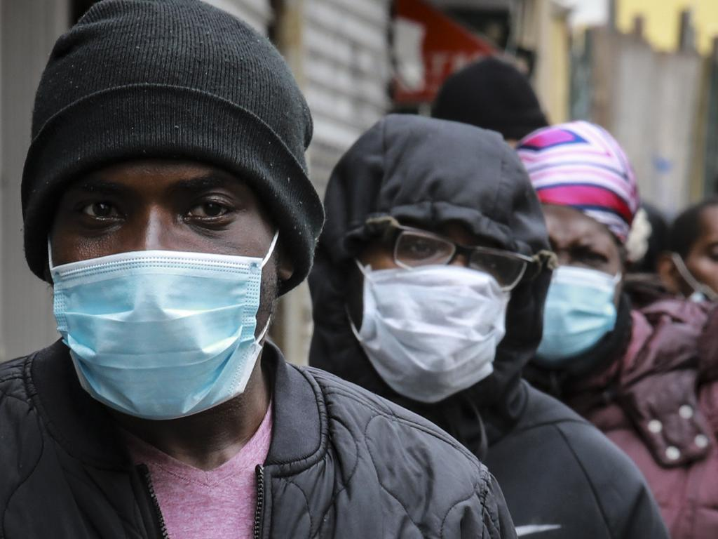 People wait for a distribution of masks and food in the Harlem neighbourhood of New York. Picture: AP
