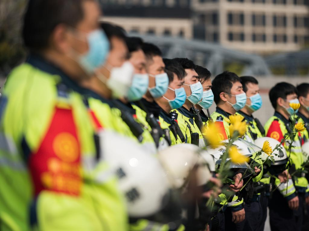 Chinese policemen wear protective masks during a national mourning to mourn victims of COVID-19 at Shanghai People's Heros Memorial Tower in Shanghai, China. Picture: Getty