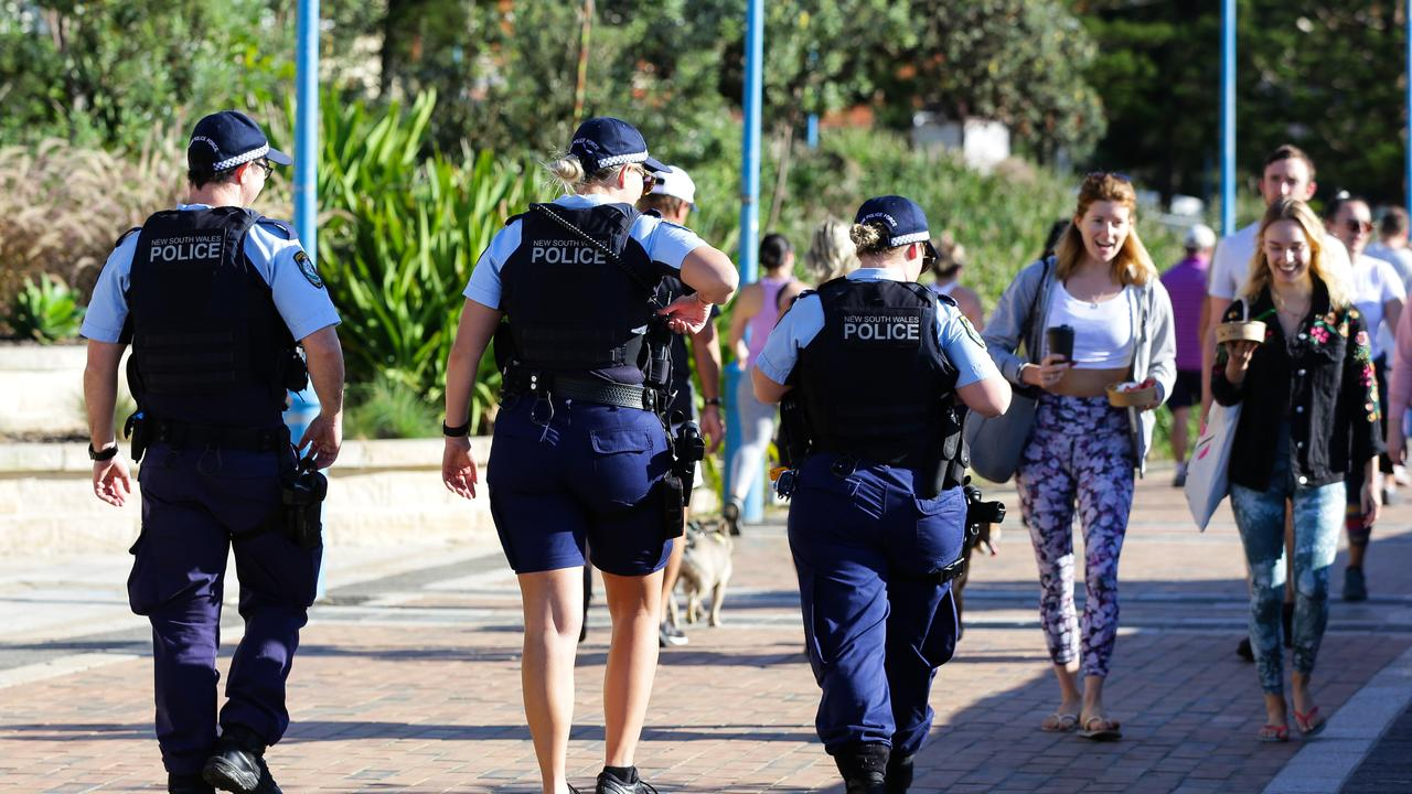 Police walk the esplanade at Coogee Beach. Picture: Gaye Gerard