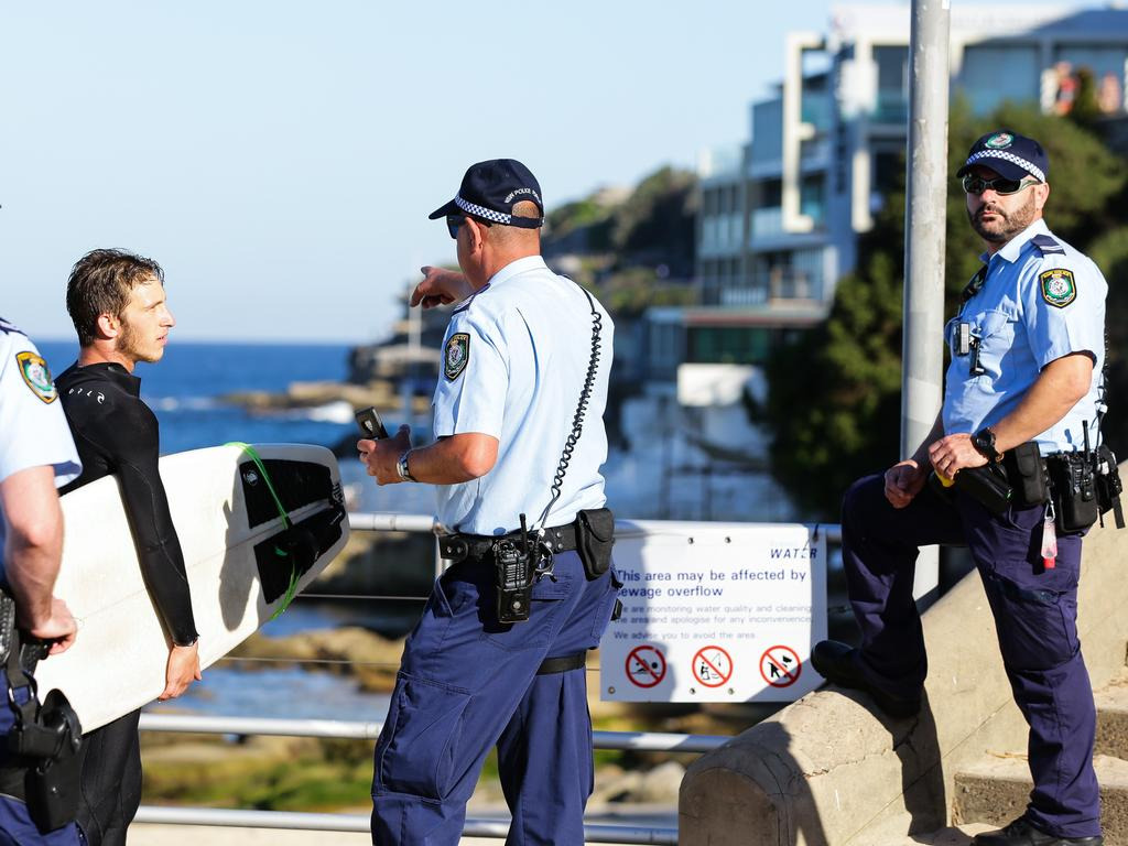 A lone surfer is found surfing out the back of Bondi Beach greeted by the Police as he came in to shore in Bondi, Sydney, April 25 2020. Picture: Gaye Gerard/ Sunday Telegraph