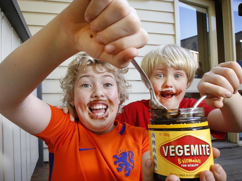 Brothers Max 11 and Alex 6 enjoying their Vegemite by the spoonful while at home. Picture: David Caird