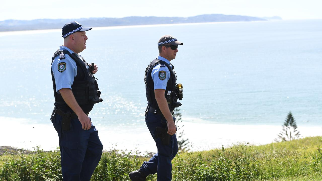 Police talk to surfers about why they are at Pat Morton lookout as they seek to ensure only locals are exercising in the area.