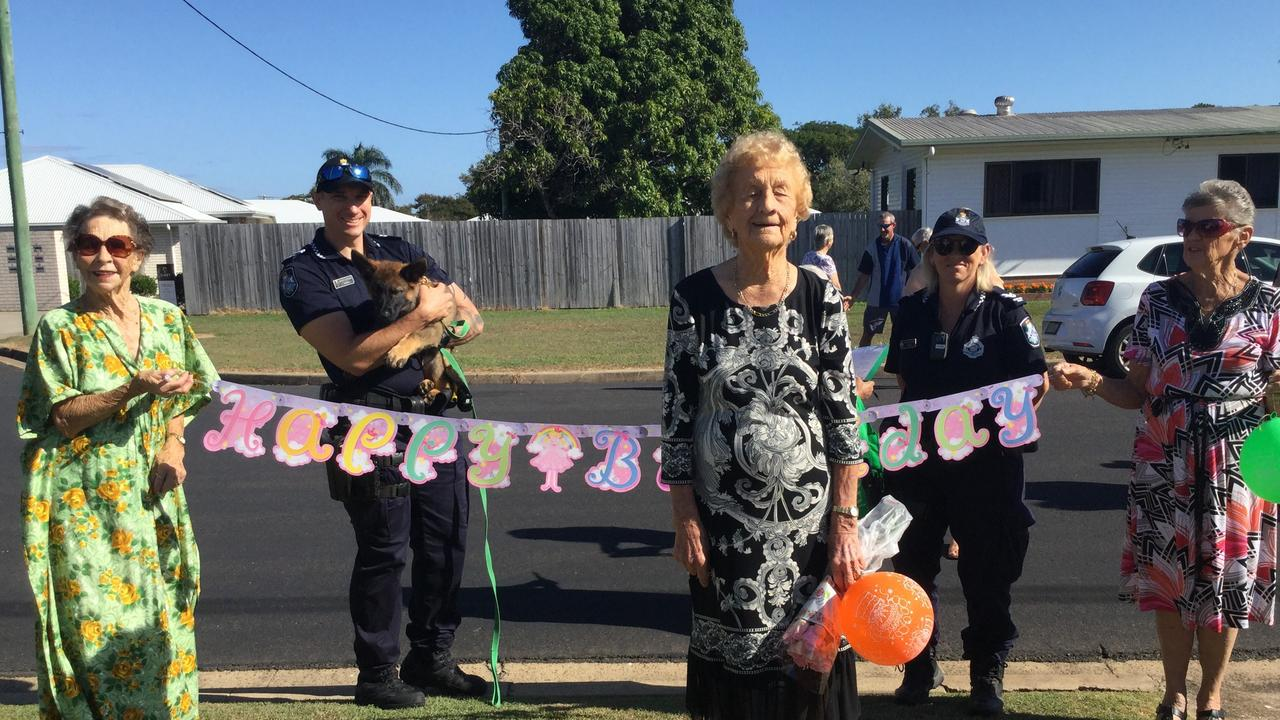 Mary Mills celebrating with Verlie Climpson, Constable Luke Giese and police dog Uzi, Senior Constable Karen McNish and Val Russell.