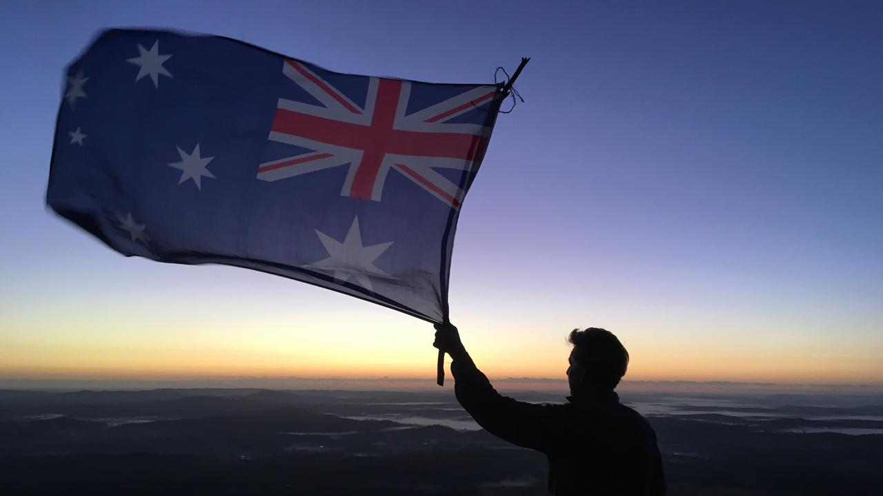 Glen Thompson raises the flag high on Mt Walsh during a private dawn service at Biggenden.