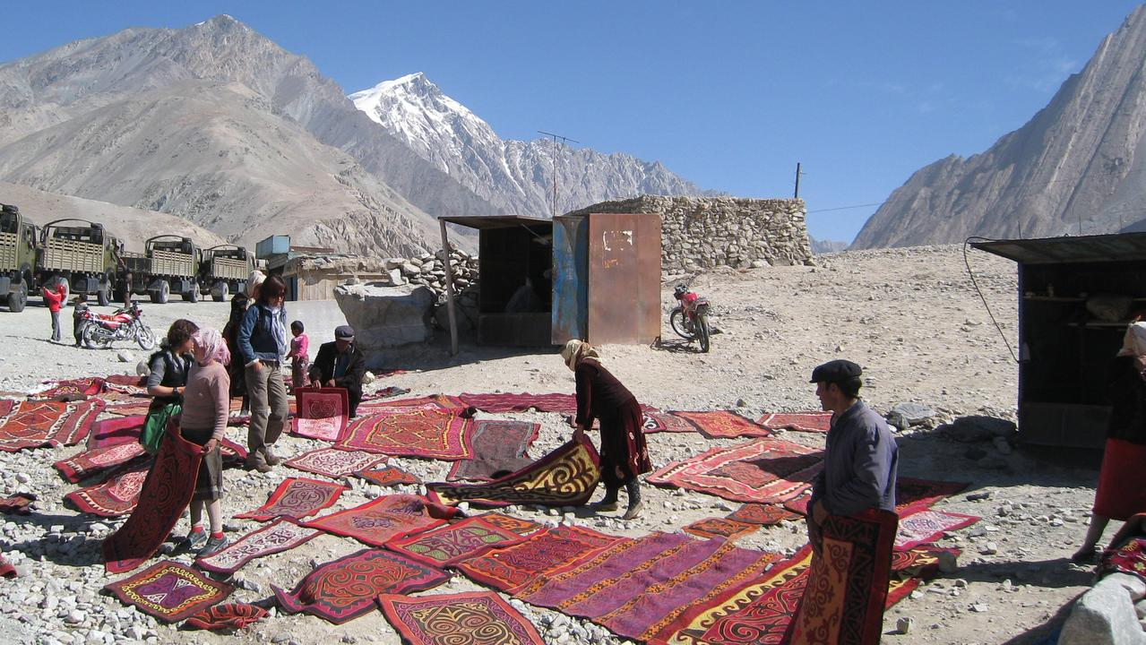 Uyghur women selling silk rugs in northwest China.
